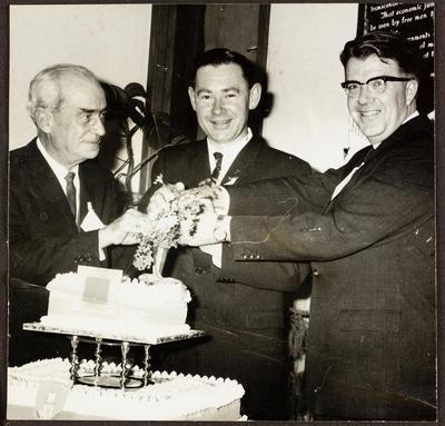 Three men cut a cake