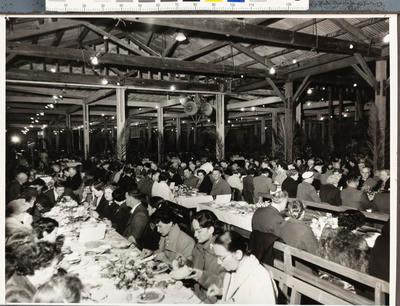 Unknown large group of people dining in rows