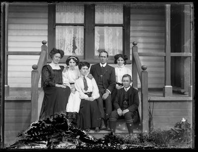 Group of six on house steps.