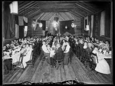 Large gathering at tables in flag decorated hall.