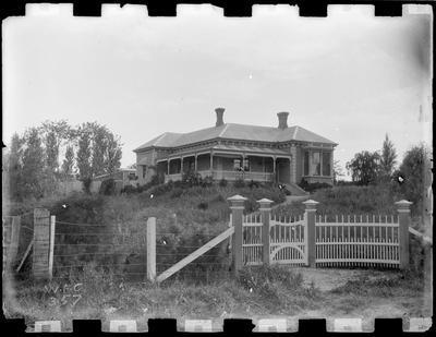 Bay villa with L shaped verandah and fine wooden gates.
