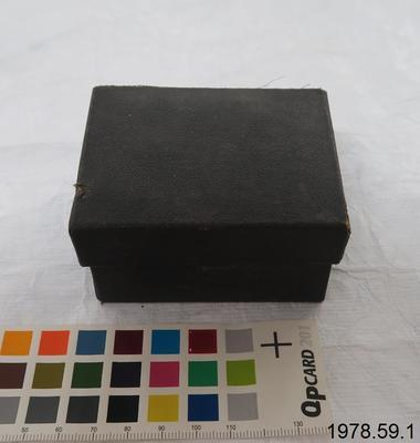 """Black card box with hinged lid and hinged front panel: """"THE CITY"""" LINEN MARKER. The label for the kit is inside the lid. When the lid (with sides) is opened, the front panel of the box falls outwards. Affixed to the inside of the front panel of the box is a small black inkpad. The box contains two rubber stamps, and a wood circular base encircled by a wood ring. On one stamp is: W. D. Lysnar; on the other: J. E. Lysnar. Handwritten in blue ink on the base of the box is: W m. D. Lysnar."""