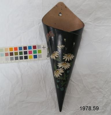 Black painted wall holder, conical shaped, painted with white daisies and bluebells with a butterfly top proper right.
