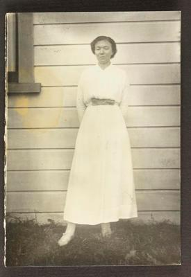 Woman standing beside house