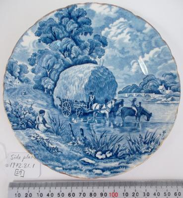 """Bread plate: blue and white, with gilded rim. The plate features a rural scene: a seated woman in the foreground, hay wagon, three horses and two figures in the middle ground, and two dwellings, a bridge, trees and sky in the background. On base: """"H [standing lion] M / SUTHERLAND CHINA / MADE IN ENGLAND / """"RURAL SCENES"""" / BONE CHINA""""."""