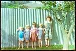 Five Children Standing Against a Fence
